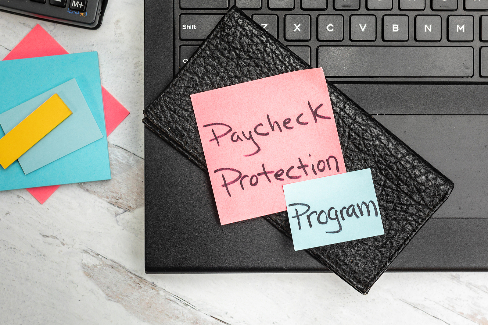 a notebook with sticky notes, paycheck protection program